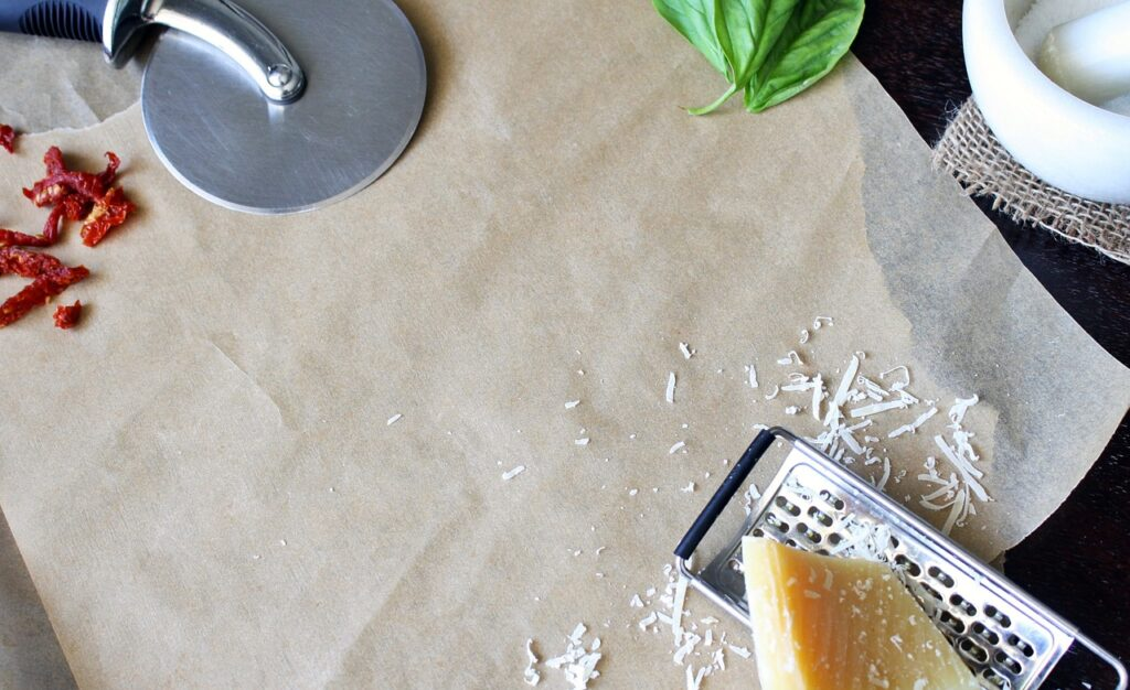 parchment paper on table with pizza cutter and cheese and cheese grater