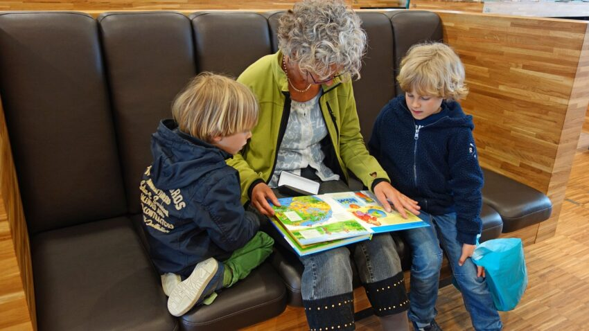 grandma with a book open reading to her two grandchildren
